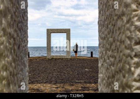 Gijon, Spanien, 02/03/2015 - Direkt neben der Skulptur von Kan Yasuda' Tensei Tenmoku' - 'Door ohne Tür, dieser Besucher schaut in den vastnes - Stockfoto