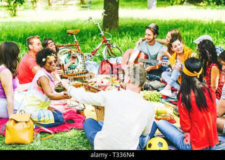 Eine Gruppe von Freunden ein Picknick genießen, beim Essen und Trinken Rotwein sitzen auf Decke in einem Park im Freien - junge Menschen, die eine lustige Begegnung - Stockfoto