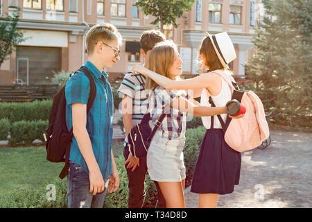 Lächelnd Freunde treffen Jugendliche in der Stadt, glückliche junge Leute Begrüßung, umarmen, fünf. Freundschaft und Personen Konzept. - Stockfoto