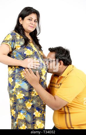 Bild des Menschen ist das Küssen der Bauch der seine schwangere Frau. Auf den weißen Hintergrund isoliert. - Stockfoto