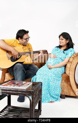 Bild des Menschen ist Gitarre spielen zu seiner schwangeren Frau. Auf den weißen Hintergrund isoliert. - Stockfoto