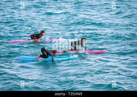 TAURANGA NEUSEELAND - 5. NOVEMBER 2012; Drei junge Frau auf hellen paddle Board am türkisblauen Meer von Mount Maunganui - Stockfoto