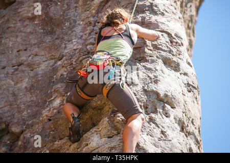 TAURANGA NEUSEELAND - 8. NOVEMBER 2012; junge unternehmungslustige Person rock bis Klettern Schere auf der Seite Mount Maunganui - Stockfoto