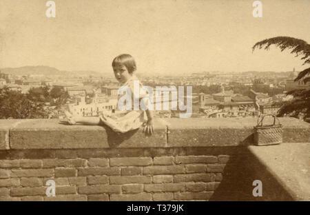 Kleines Mädchen sitzt auf einer Wand an Gianicolo, Rom, Italien 1920 s - Stockfoto
