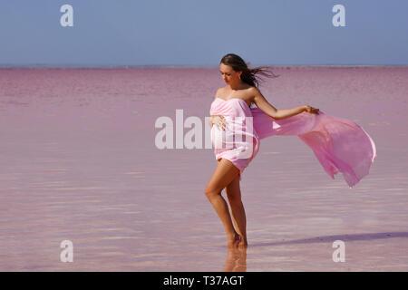 Schöne junge schwangere Frau genießen die Sonne am Strand, rosa See - Stockfoto