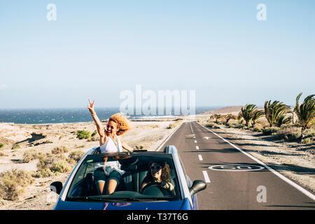 Gerne fröhliche Paar der jungen kaukasischen verrückte Frau mit lockigem Haar genießen Sie die Reise und Aufenthalt außerhalb der Dach von einem Cabrio mit - Stockfoto