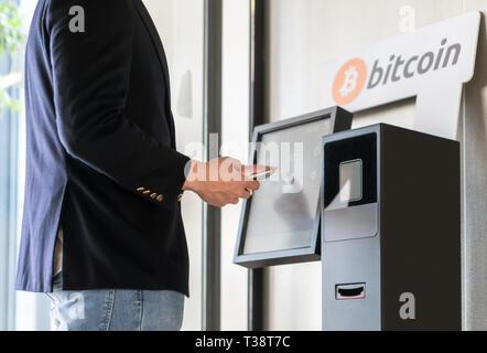 Geschäftsmann Kauf und Übertragung cryptocurrency zu Handy von ATM Maschine für den Kauf und Verkauf von cryptocurrency. - Stockfoto