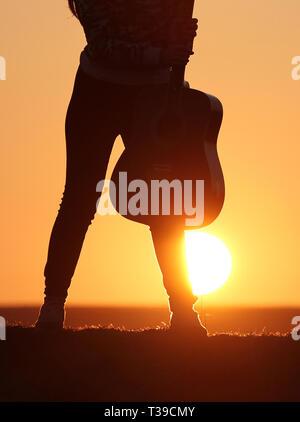 Silhouette der Gitarrist bei Sonnenuntergang, Mädchen, Gitarrist, Silhouette einer Gitarre, Musik - Stockfoto