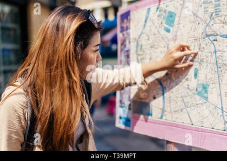 Junge weibliche touristische Frau an den Stadtplan und Wegbeschreibung in verwirrt in Bangkok, Thailand Suche Suchen - Stockfoto