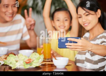Junge asiatische Frau unter selfie mit ihrer Familie beim Abendessen - Stockfoto