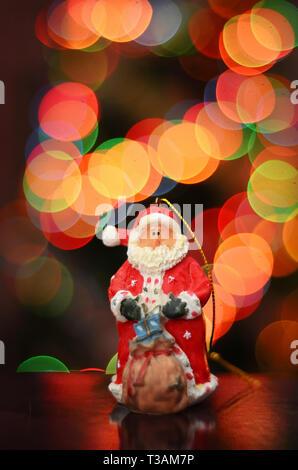 Spielzeug Santa in einem roten Outfit mit einem Beutel der Geschenke für das neue Jahr auf dem Hintergrund der bunten Bokeh von der festlichen Beleuchtung auf dem Weihnachtsbaum - Stockfoto