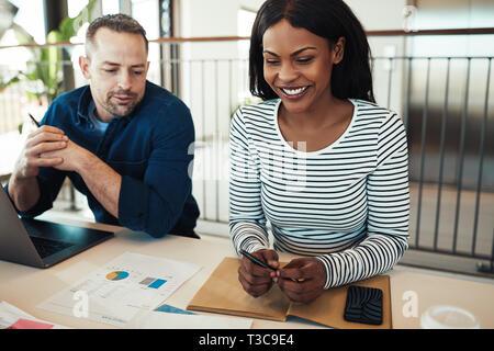Zwei verschiedene Kollegen Lächeln und Schreibarbeit gemeinsam diskutieren, während an einem Schreibtisch in einem modernen Büro sitzen - Stockfoto