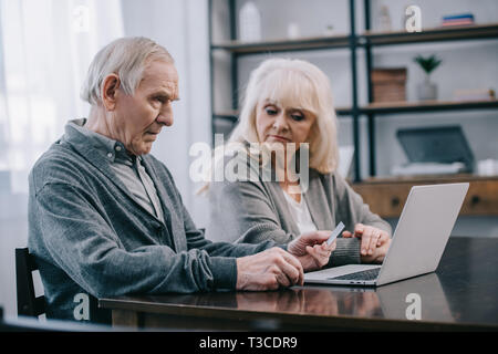 Senior Paar sitzen am Tisch und mit Laptop zu Hause - Stockfoto