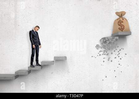 Traurig Geschäftsmann auf grauem Beton Treppe mit grossen Geld Beutel an der Spitze, aber mit einem Teil der Schritte zwischen Unternehmer und Tasche fehlt - Stockfoto