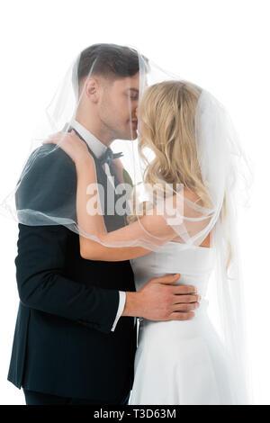 Braut Bräutigam küssen und deckt ihn mit Bridal Veil isoliert auf weißem - Stockfoto