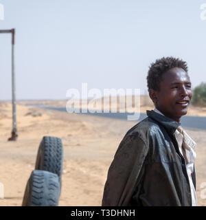 Kerma, Sudan, Februar 8., 2019: Junge Sudanesische lächelnden Mann in seitlichen Profil auf dem Weg durch die Wüste im Norden des Sudan mit alten, abgenutzten Leder jac - Stockfoto