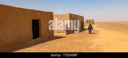 Kerma, Sudan, Februar 10., 2019: Zwei farbige sudanesischen Frauen, Shopping in ein kleines Dorf mit zwei Lehmhütten, in der Wüste. - Stockfoto