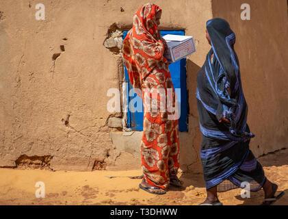 Kerma, Sudan, Februar 10., 2019: Zwei Sudanesische Frauen, eines in einem blauen Kleid, eines in einem roten Kleid, sprechen vor einer Lehmhütte in einer Wüste Dorf. - Stockfoto