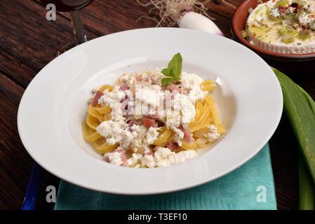 Teller Pasta Nudeln mit Hüttenkäse Speck und Zwiebeln Schalotten - Stockfoto