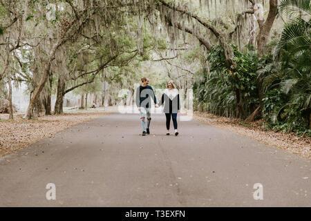 Nette Junge glücklich liebend Paar auf einem alten, verlassenen Straße mit Bemoosten Eichen überhängenden - Stockfoto