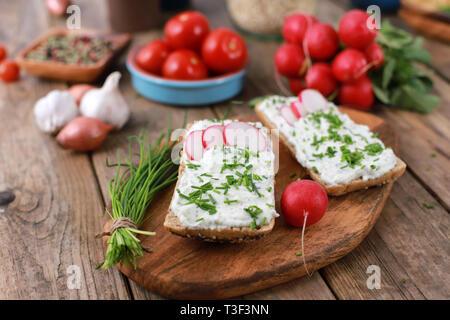 Vollkornbrot mit Quark und frischem Schnittlauch, Radieschen und Tomaten auf einem rustikalen Holztisch - gesundes Frühstück mit frischen Kräutern - Stockfoto