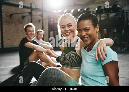 Zwei passen junge Frauen in Sportkleidung Lachen beim Sitzen, Arm in Arm zusammen auf dem Boden einer Turnhalle nach dem Training - Stockfoto