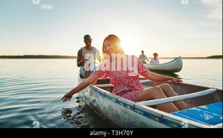 Lächelnden jungen Frau tauchen ihre Hand in der See Wasser beim Paddeln in einem Kanu mit ihrem Freund und Freunden auf einen späten Sommernachmittag - Stockfoto