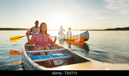 Lächelnden jungen Frau und ihrem Freund einen Tag Kanu mit Freunden auf einem See auf einem späten Sommernachmittag - Stockfoto