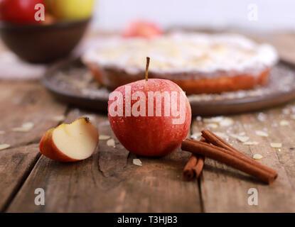 Apfelkuchen - frische Äpfel und zimtstangen vor einem hausgemachten Apfelkuchen auf einem rustikalen Holztisch - Stockfoto