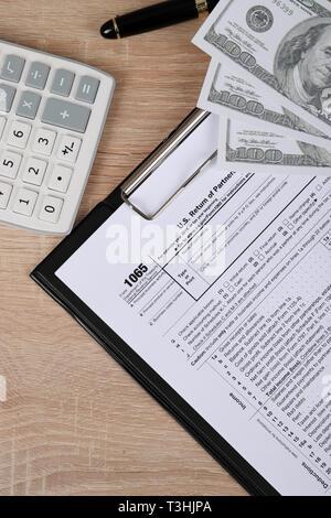 1065 Steuerformular liegt in der Nähe von hundert Dollar bil und Taschenrechner auf einen Tisch. Uns parentship Einkommen - Stockfoto