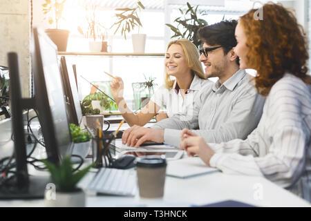 Junges Projekt Team gemeinsam auf den Computern im Büro
