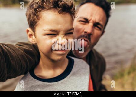 Nahaufnahme von einem Kind in der Nähe von einem See mit seinem Vater, die Gesichter hinter ihm. Vater und Sohn die Zeit gemeinsam Spaß im Freien. - Stockfoto