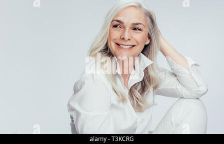Schöne ältere Frau in Weiß casuals weg schauen und lächeln. Heiter, reife Frau sitzen auf weißem Hintergrund. - Stockfoto