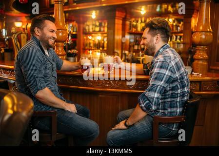 Zwei männliche Freunde trinkt Bier an der Theke im Pub - Stockfoto