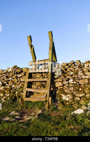 Eine Leiter zauntritte Überqueren einer Trockenmauer in Derbyshire, Großbritannien. - Stockfoto