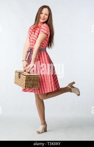 Junge fröhliche Frau im roten Kleid mit Picknick Korb im Studio auf weißem Hintergrund posiert - Stockfoto