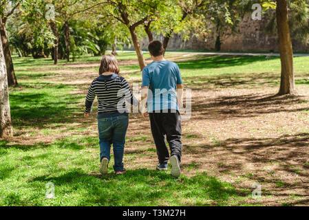 Zwei junge Männer und Frauen mit Down-syndrom zu Fuß auf dem Rücken, Hände halten, die gegenseitige Zuneigung. - Stockfoto