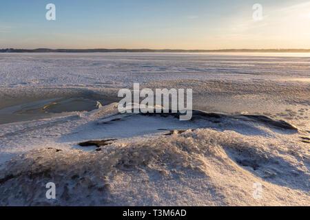 Ruhigen Landschaft von Eis, Schnee, Fels und Eis eingefroren und verschneiten See in Finnland im Winter an sonnigen Morgen. - Stockfoto