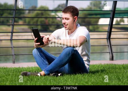 Schöner Junge mit Tablet und Kopfhörer, Kaffee trinken zu gehen, Mann sitzt auf Gras und schöne sonnige Tag am Fluss Seite. Modell Fotoshooting. - Stockfoto