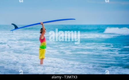 Ein Surfer wartet auf die richtige Welle im St. Johns County Ocean Pier, 20. März 2016, in St. Augustine, Florida. - Stockfoto