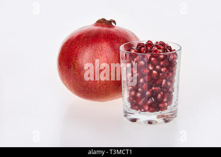 Close-up des Granatapfels Samen in ein Glas auf einem weißen Hintergrund, Ansicht von oben. Rote granat Obst reif. Granatapfel Saft in ein Glas. Frische Granat - Stockfoto