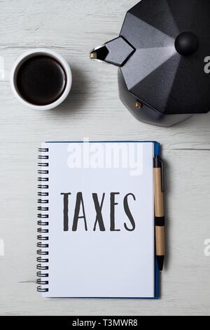 Hohe Betrachtungswinkel eines Notebooks mit dem Wort Steuern in der ersten Seite geschrieben, ein Paar schwarze Kunststoff umrandet Brillen, einer Tasse Kaffee und einem moka Topf auf - Stockfoto