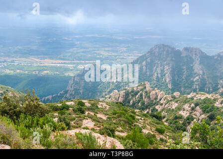 Hazy ungewöhnliche Berge mit grünen Bäumen und bewölkter Himmel in der Nähe von Kloster Montserrat, Spanien. Katalonien