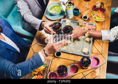 Hände von Freunden, die zusammen im Kreis mit den verschiedenen Cocktails mit Eis auf dem Hintergrund der alten Holztisch Oberfläche. Ansicht von oben. - Stockfoto