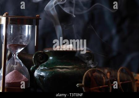 Alte Sanduhr und Brillen in der Nähe von erloschen Kerze mit Rauch - Stockfoto