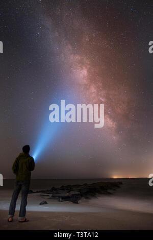 Asiatischer Mann leuchtende Taschenlampe am Sternenhimmel - Stockfoto