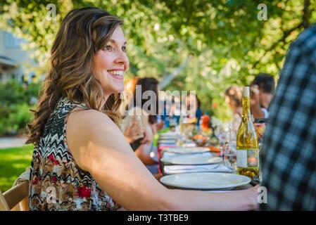 Portrait von lächelnden kaukasische Frau am Tisch bei der Party im Freien sitzen - Stockfoto