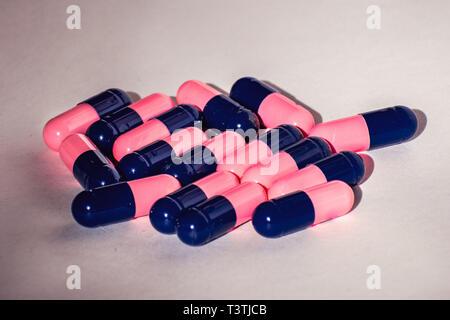 In der Nähe von Rosa und Blau Antibiotika Amoxicillin capsule Pillen. Konzept für antimikrobielle Resistenz; Pharmaindustrie; Global Healthcare - Stockfoto
