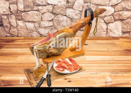 Spanischer Serrano Schinken auf das Bein mit Holz Inhaber auf einem Tisch - Stockfoto