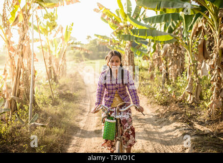 Asiatische Frau Reiten Fahrrad auf Landstraße - Stockfoto